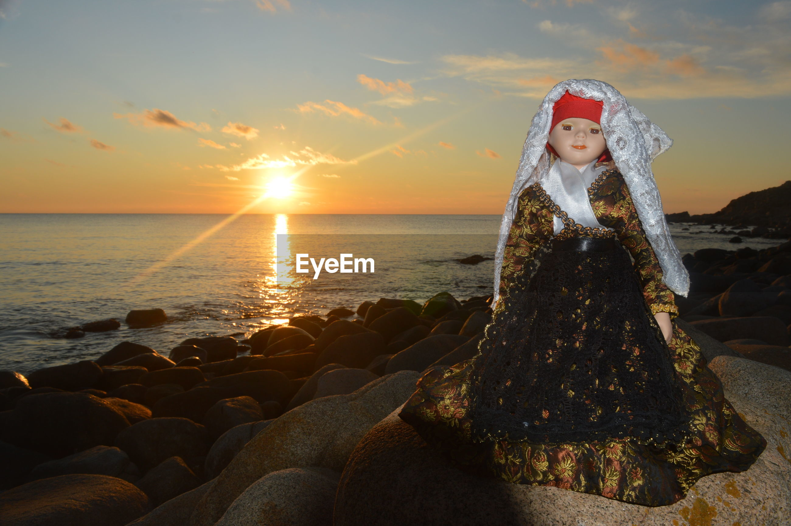 Doll on rock against sea during sunset