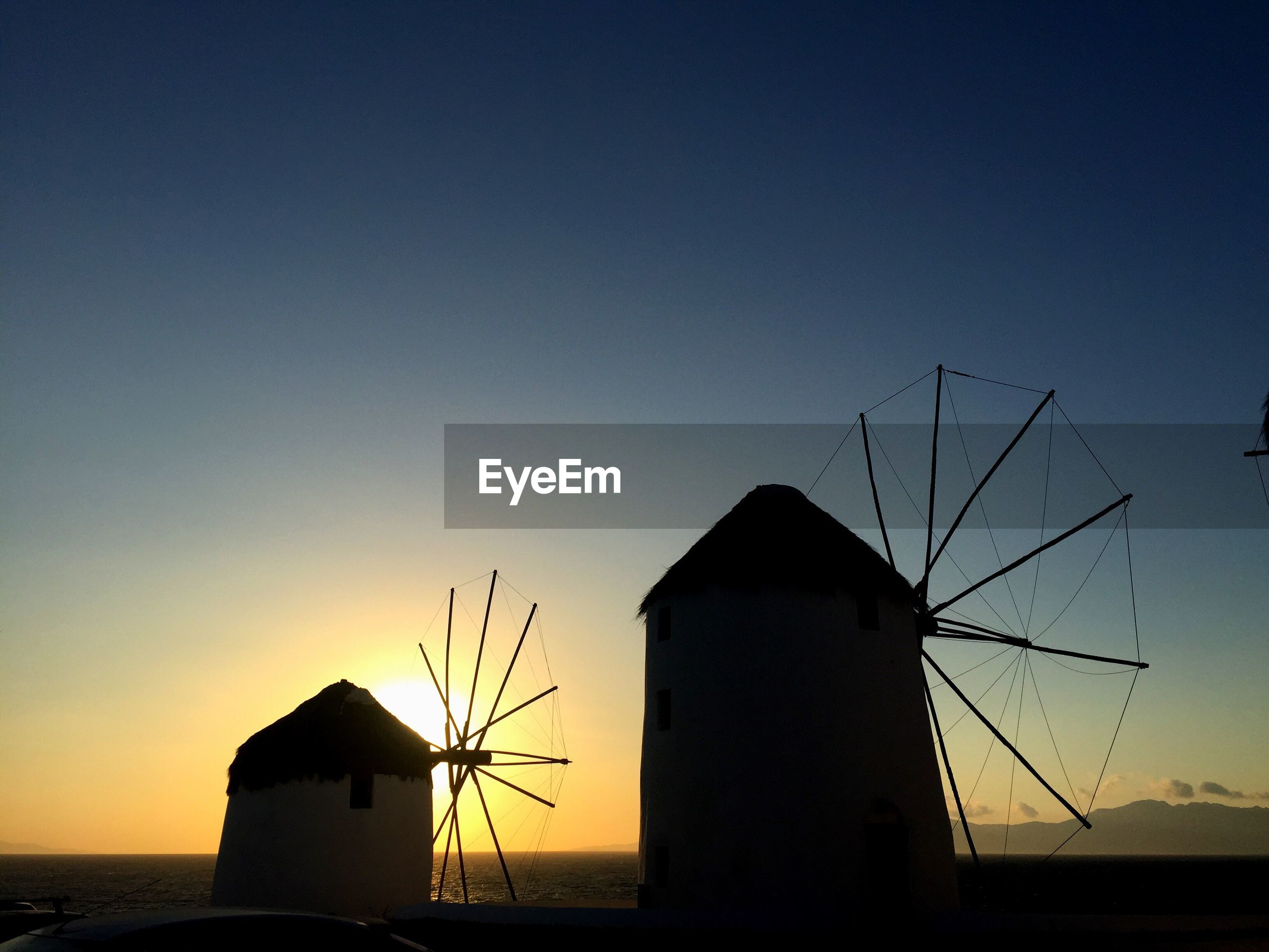 SILHOUETTE OF TRADITIONAL WINDMILL AGAINST SKY