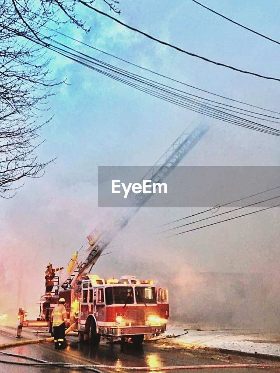 smoke - physical structure, transportation, firefighter, commercial land vehicle, spraying, sky, outdoors, water, day, destruction, land vehicle, electricity pylon, fire engine, men, people