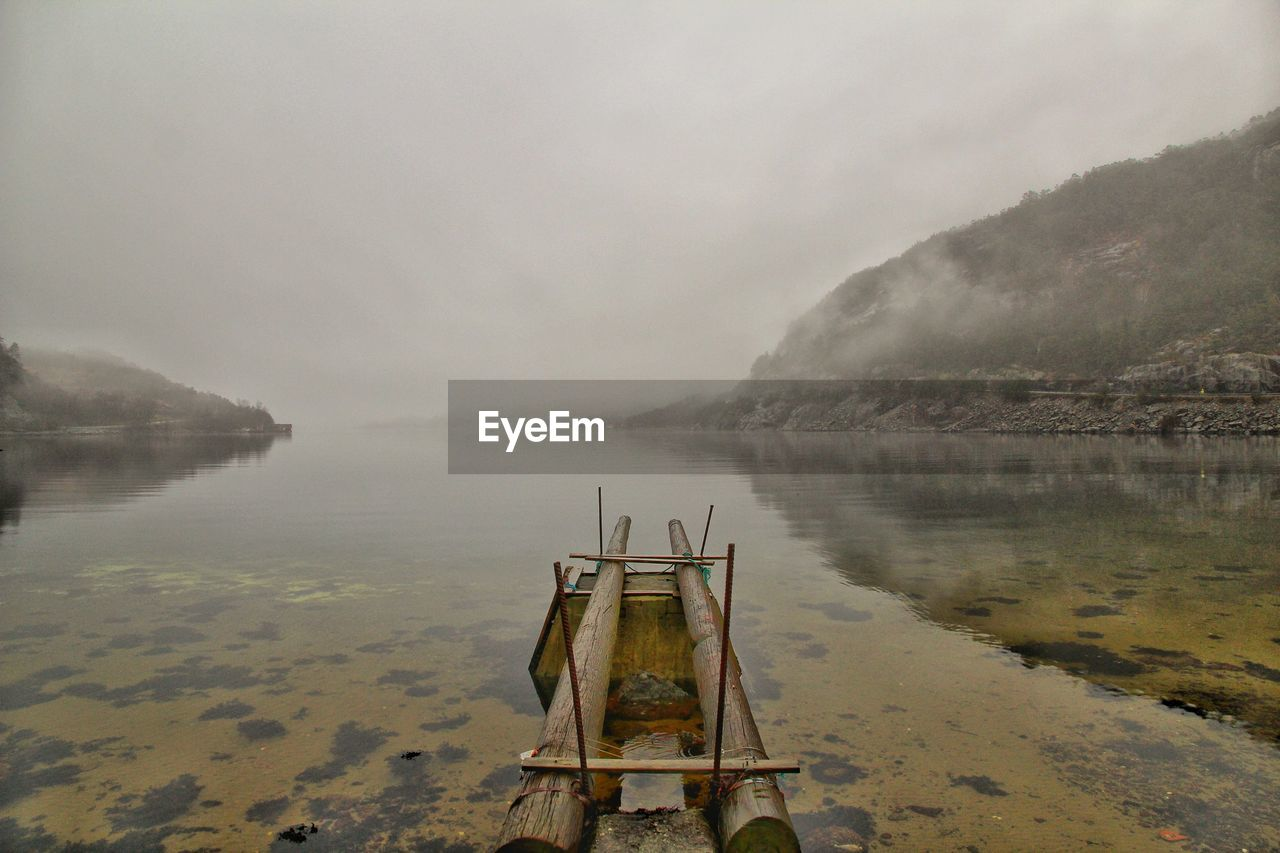 water, fog, nature, tranquility, lake, day, beauty in nature, sky, scenics - nature, no people, tranquil scene, mountain, cold temperature, non-urban scene, winter, outdoors, built structure, architecture, rain