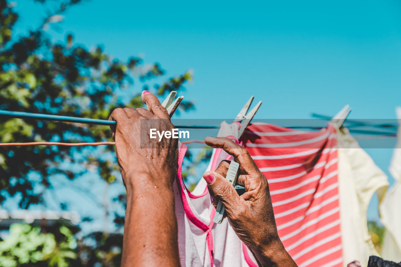 real people, day, nature, sky, clothesline, blue, men, one person, focus on foreground, rope, holding, laundry, outdoors, clothespin, lifestyles, leisure activity, hand, human body part, sunlight, finger, human limb