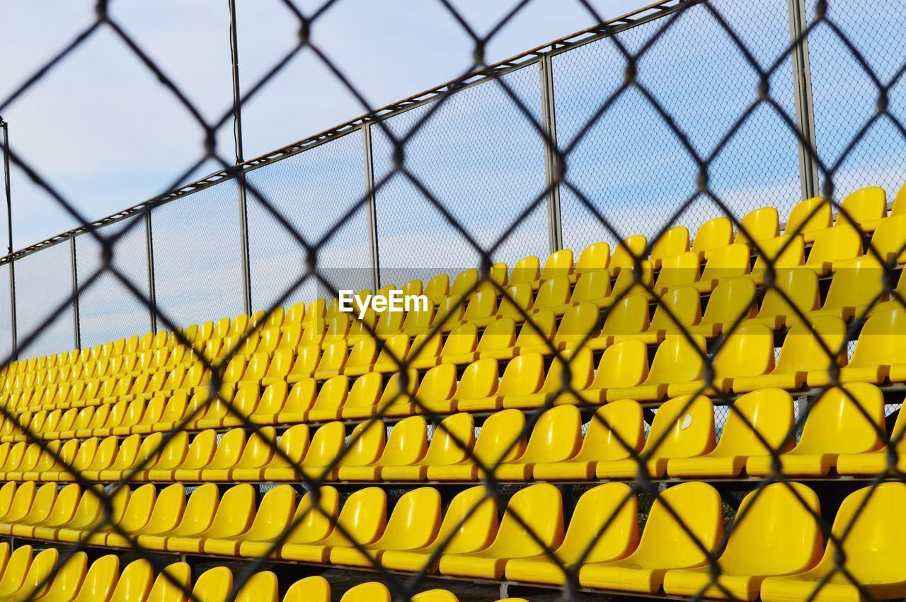 Close-Up Of Yellow Chainlink Fence Against Bleachers