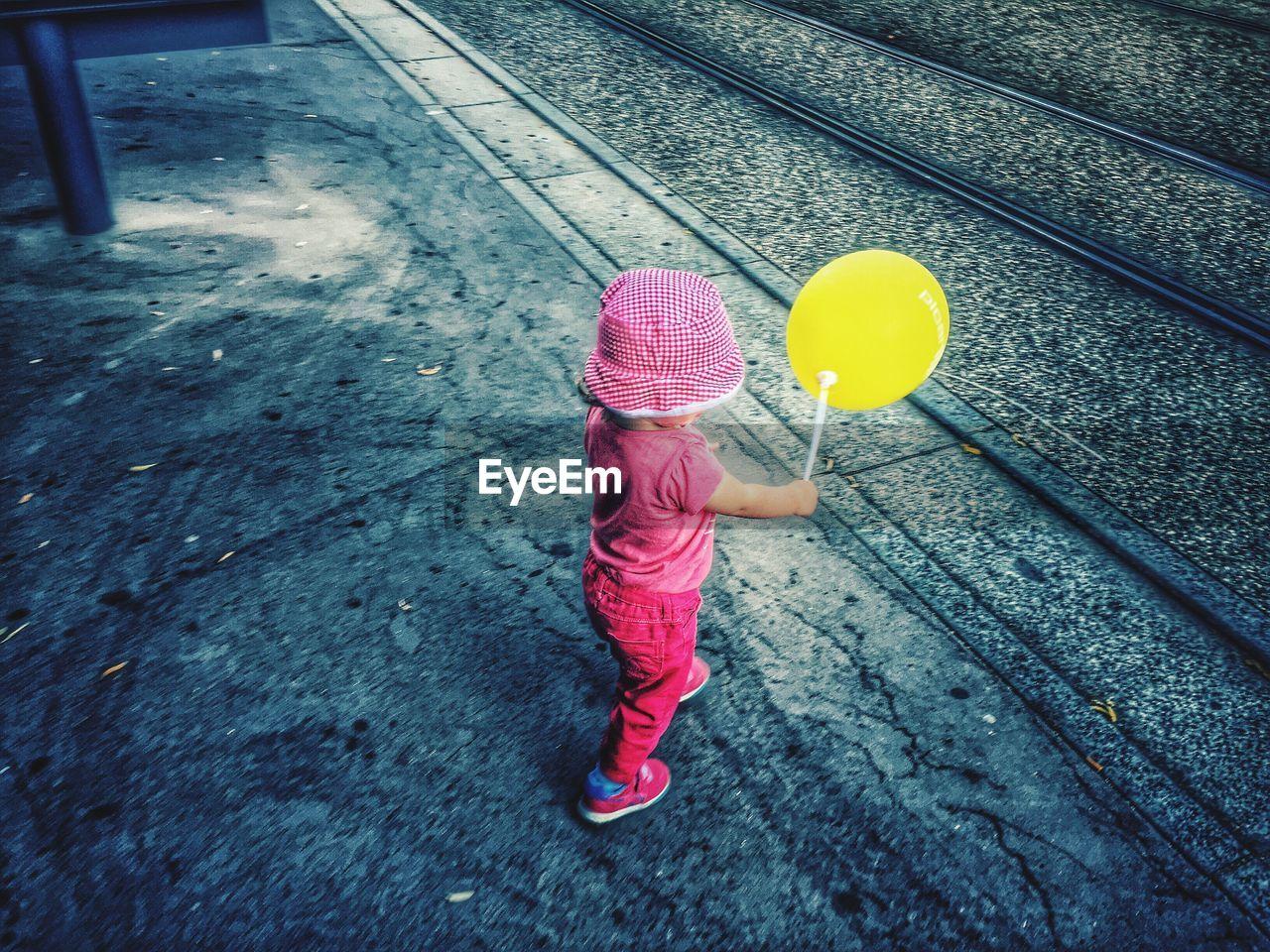 Full length of girl with yellow balloon walking on sidewalk