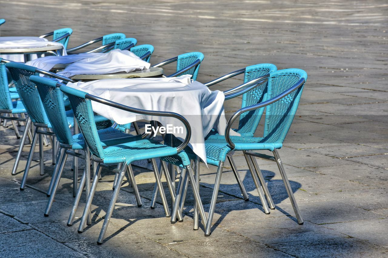 chair, seat, blue, no people, absence, day, table, empty, wood - material, group of objects, footpath, outdoors, nature, still life, land, flooring, sidewalk, white color, relaxation, arrangement