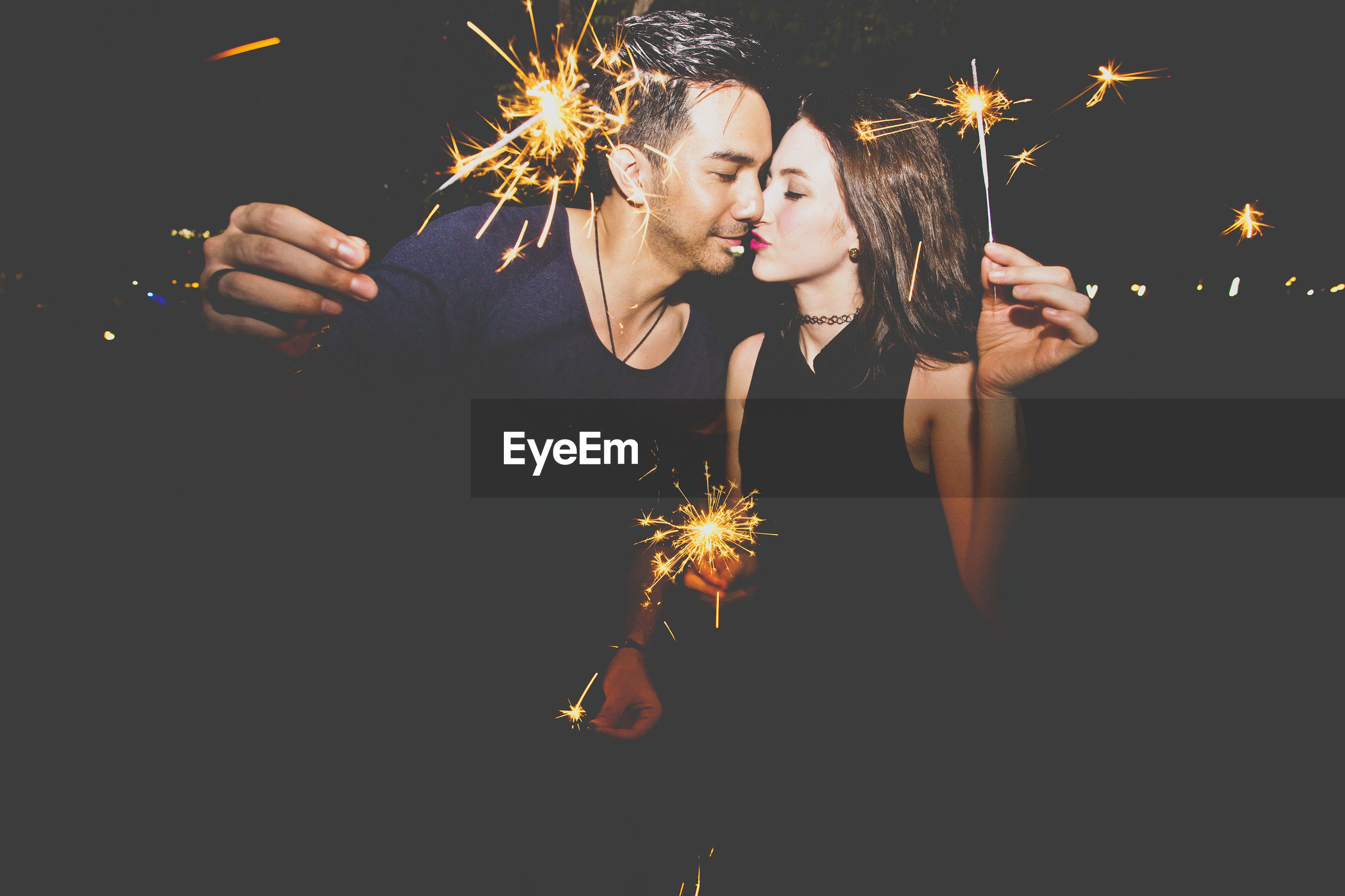 Young couple kissing while holding burning sparklers at night