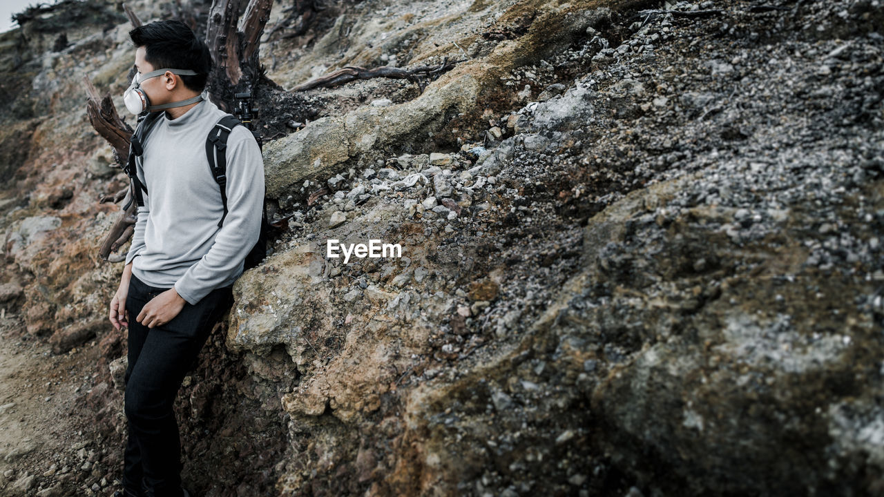 Man Wearing Pollution Mask While Standing Against Rock Formation