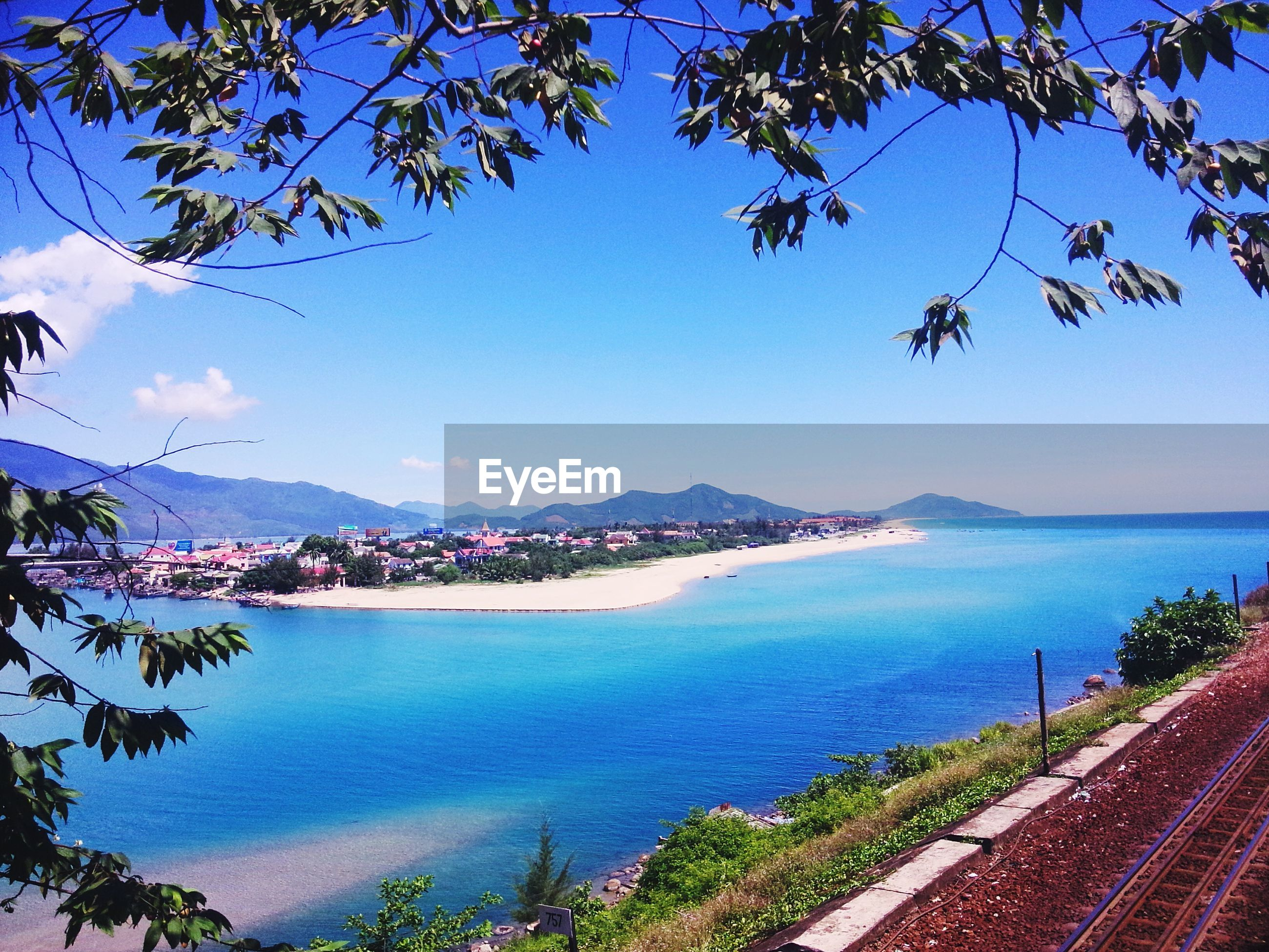water, sea, blue, mountain, tree, tranquil scene, scenics, tranquility, travel destinations, sky, mountain range, tourism, distant, city, clear sky, beauty in nature, vacations, nature, seascape, day, town, outdoors, ocean, calm, majestic, coastline, non-urban scene, city life, natural landmark, solitude