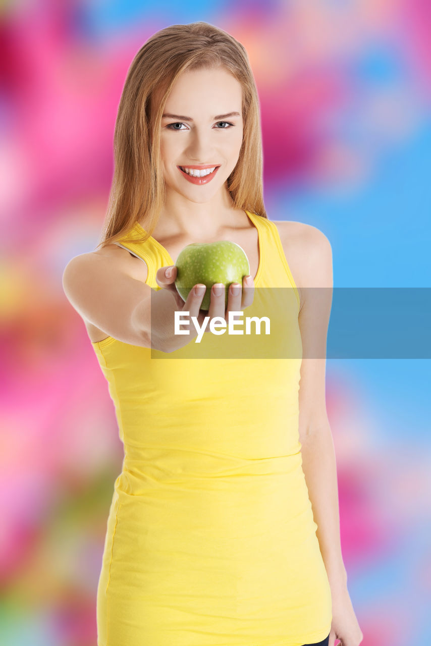 Portrait of smiling young woman holding apple against colored background