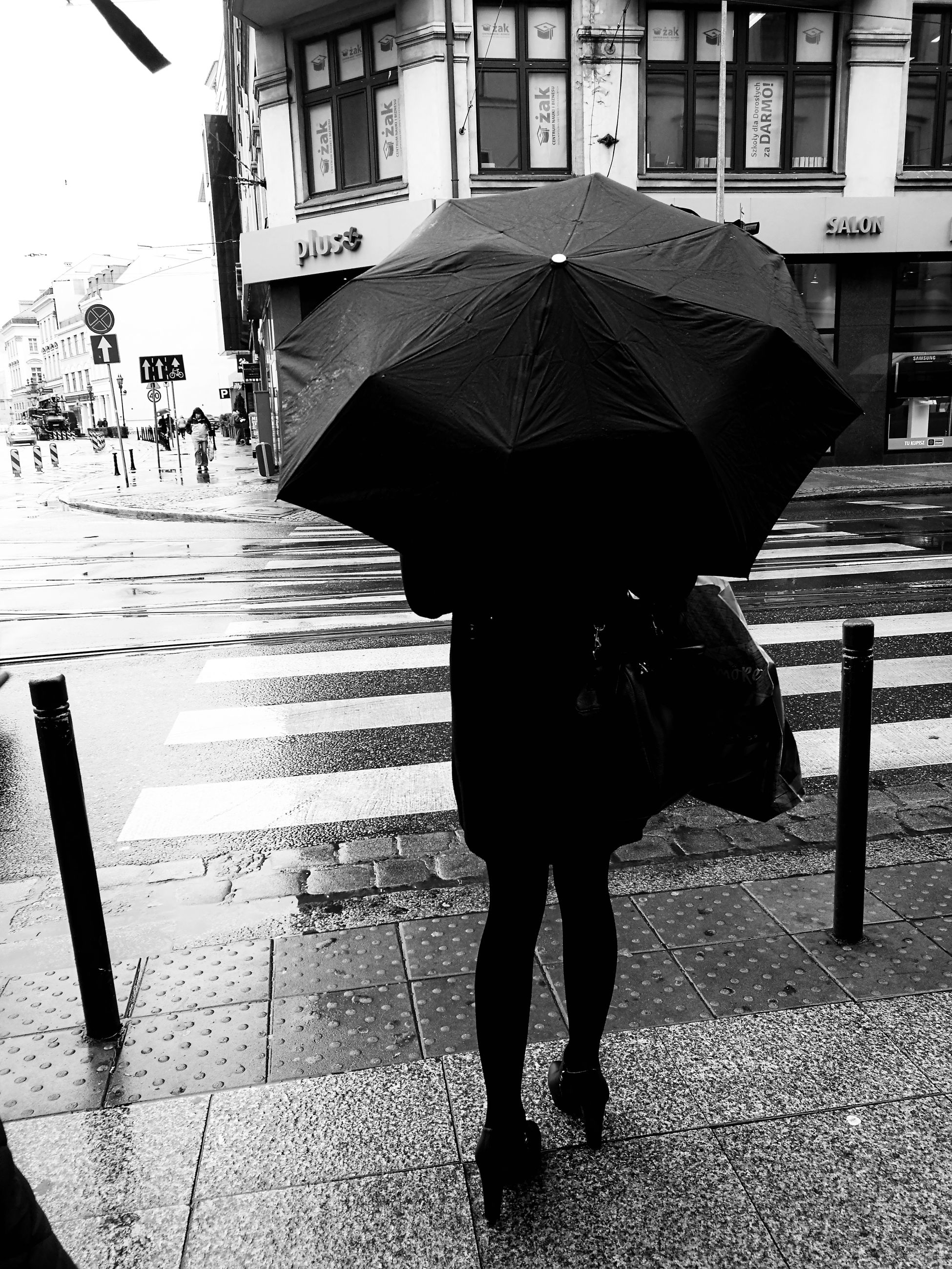 umbrella, street, season, rain, building exterior, city, weather, walking, architecture, city life, built structure, travel, rear view, rainy, protection, monsoon, wet, lifestyles, men, rainy season, road, transportation, holding, car, city street, leisure activity, water, casual clothing, day