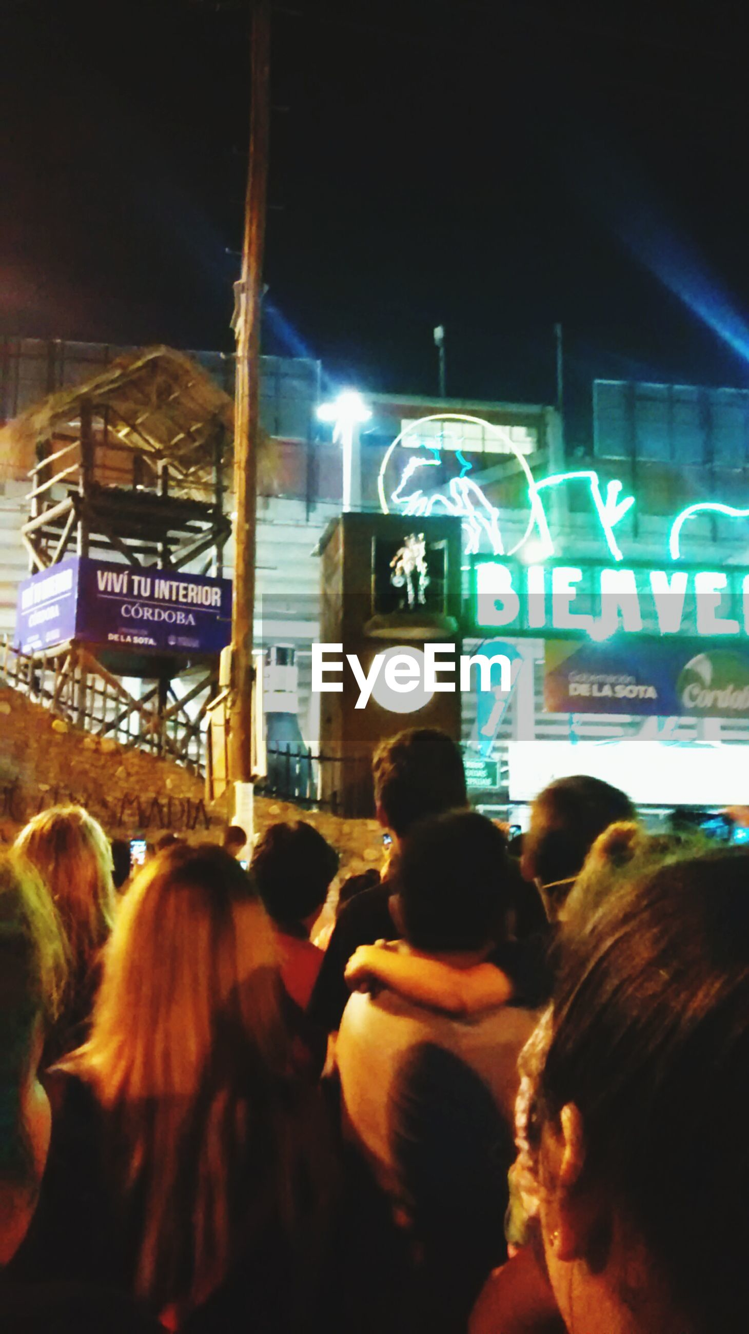 lifestyles, men, leisure activity, text, communication, illuminated, large group of people, person, western script, indoors, rear view, togetherness, night, headshot, crowd, medium group of people, standing, travel