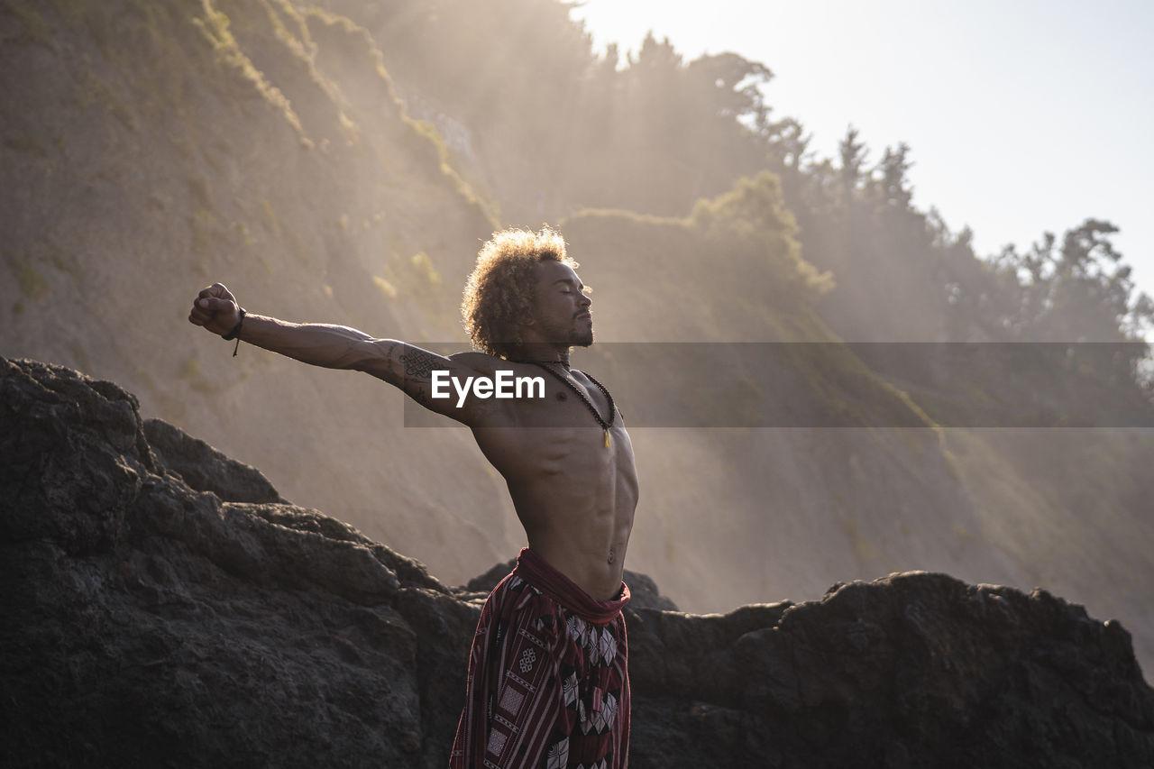 MAN LOOKING AT ROCK FORMATION