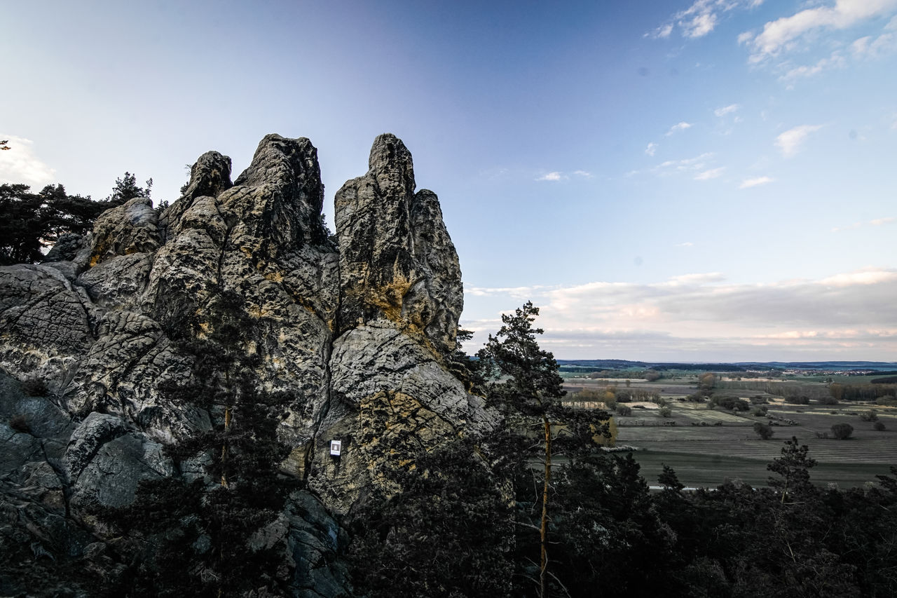 sky, beauty in nature, rock, tranquility, rock formation, scenics - nature, tranquil scene, nature, solid, no people, rock - object, water, cloud - sky, sea, land, day, idyllic, non-urban scene, mountain, outdoors, eroded, formation