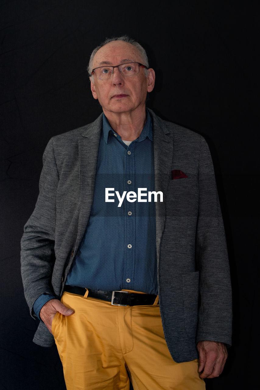 Senior man standing against black background