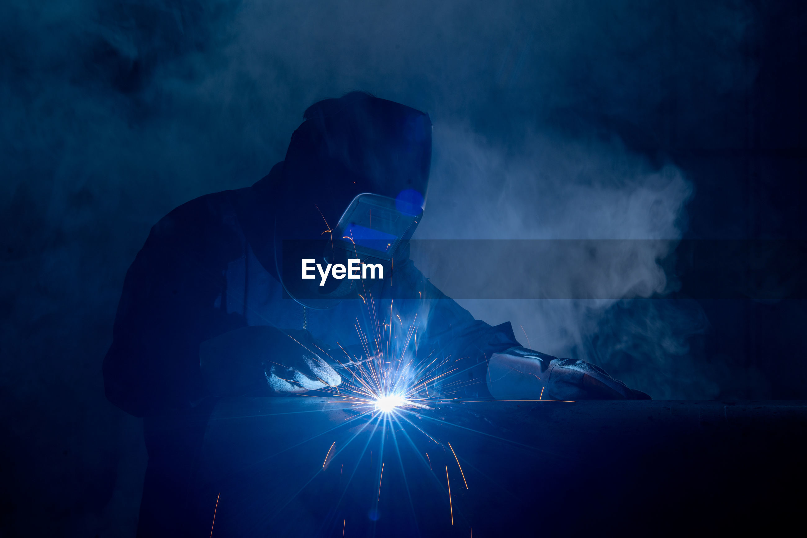 Man welding metal in workshop