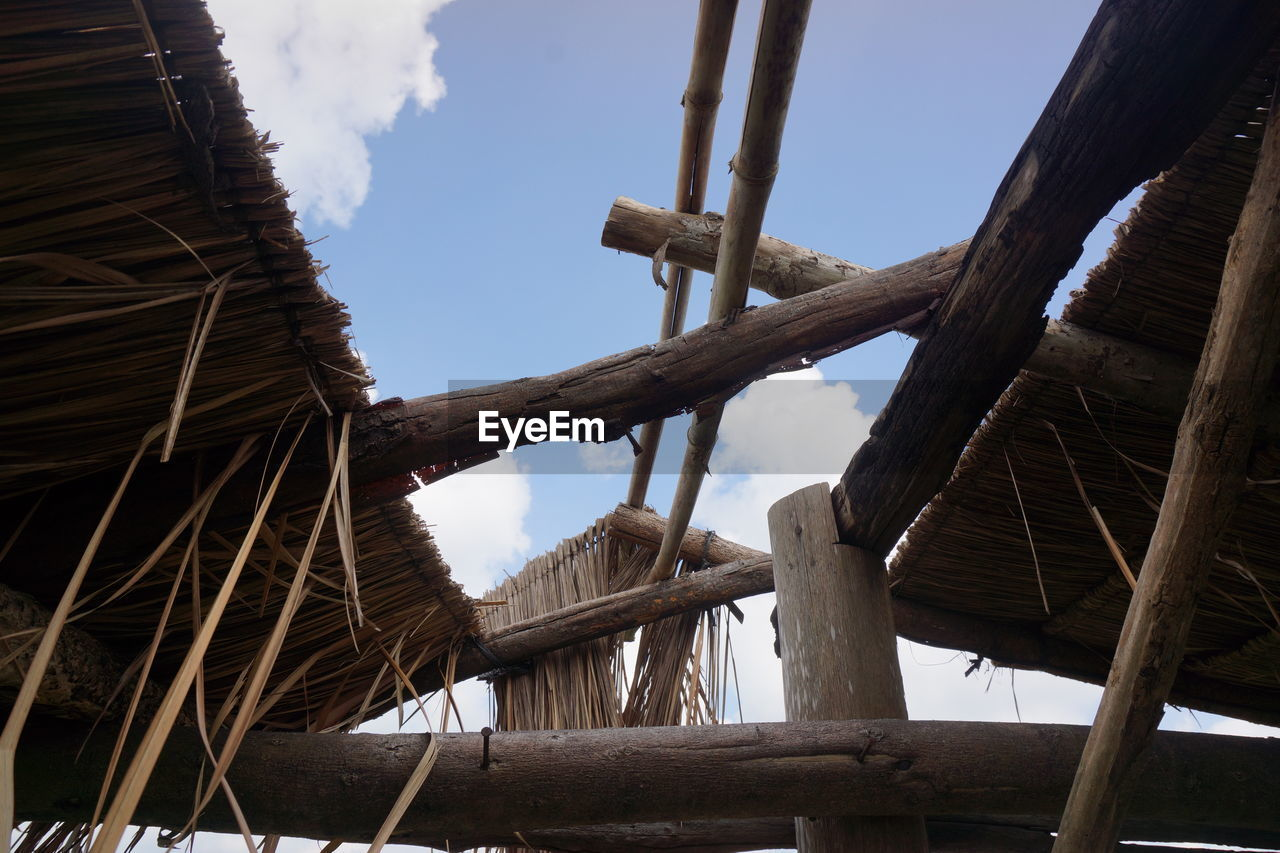wood - material, low angle view, thatched roof, sky, day, roof, timber, no people, roof beam, built structure, outdoors, architecture, shelter, tree, nature
