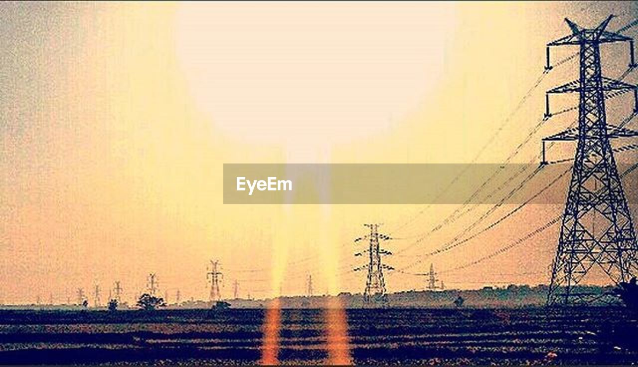 electricity pylon, cable, sunset, electricity, outdoors, sky, no people, agriculture, rural scene, landscape, scenics, tree, nature, day, telephone line, beauty in nature