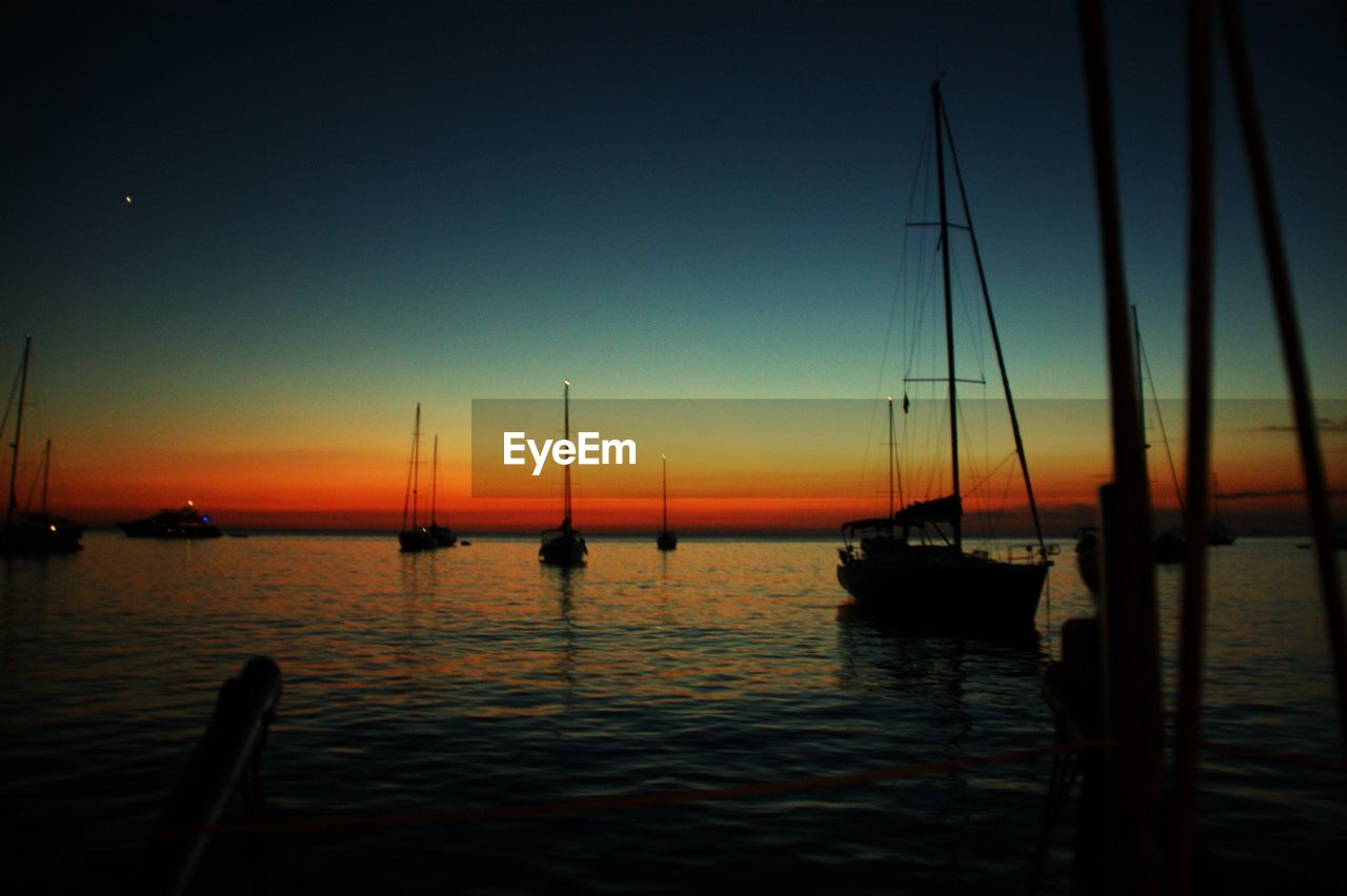 sunset, nautical vessel, transportation, water, boat, tranquility, nature, no people, outdoors, reflection, mast, mode of transport, silhouette, scenics, sea, moored, beauty in nature, sky, sailboat, sailing, clear sky, night