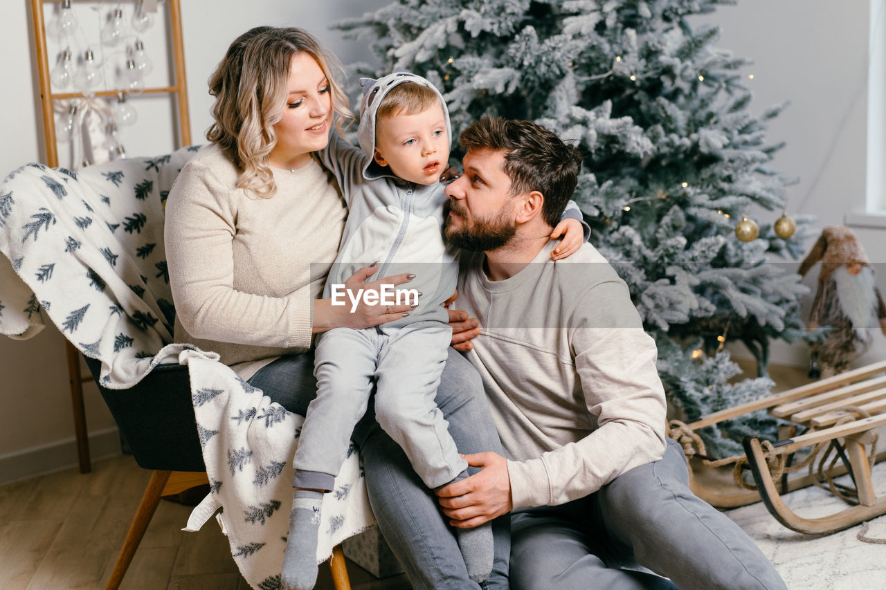 FULL LENGTH OF FATHER AND WOMAN SITTING IN CHRISTMAS TREE