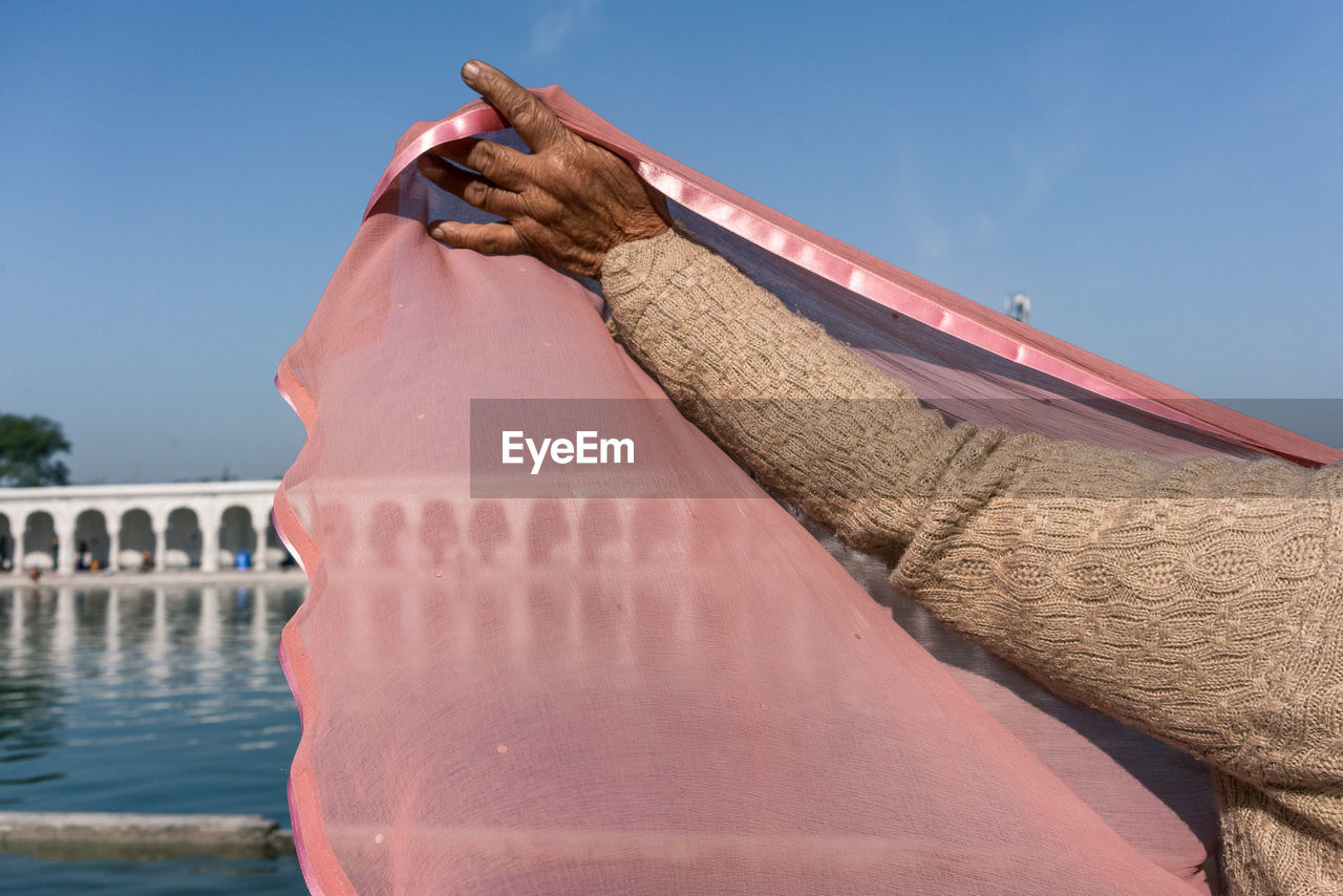 Close-Up Of Woman Lifting Pink Fabric