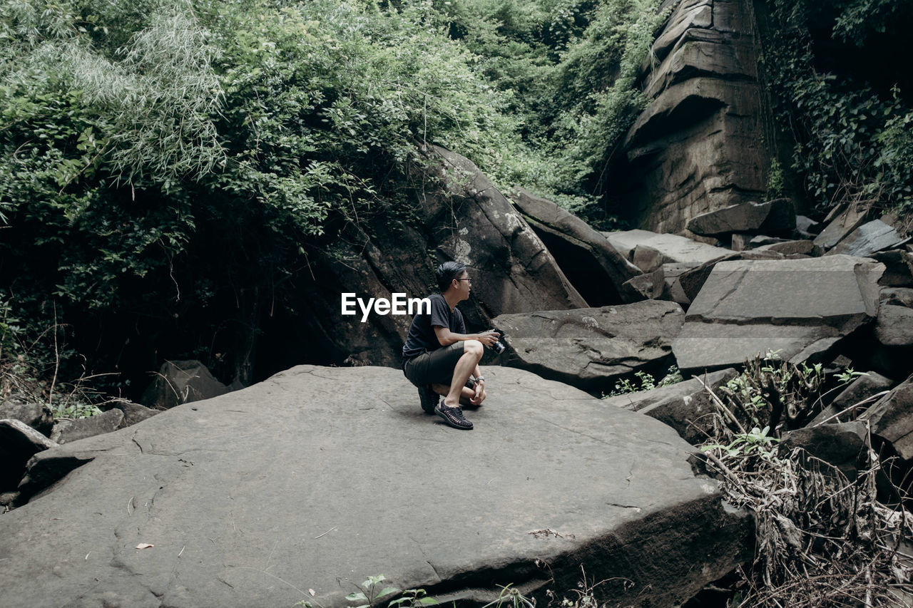Full length of young man kneeling on rock in forest