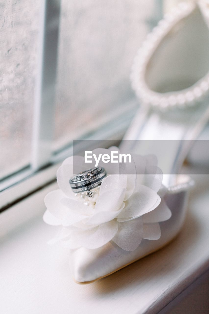 close-up, white color, no people, indoors, plant, flower, flowering plant, ring, table, freshness, jewelry, high angle view, focus on foreground, still life, selective focus, wedding, wedding ring, life events, food and drink, plate, precious gem, temptation
