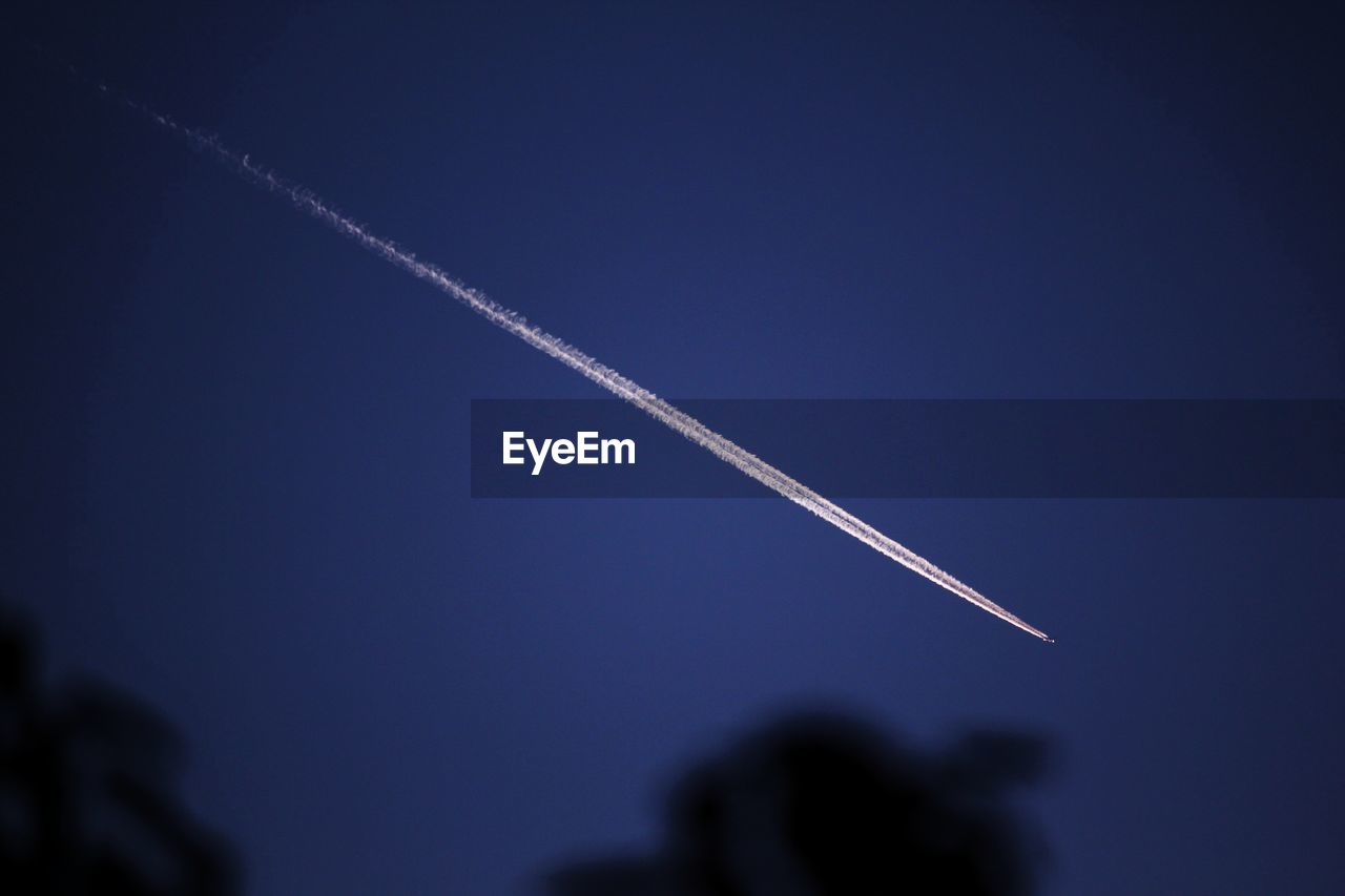 Low angle view of vapor trail in blue sky at night