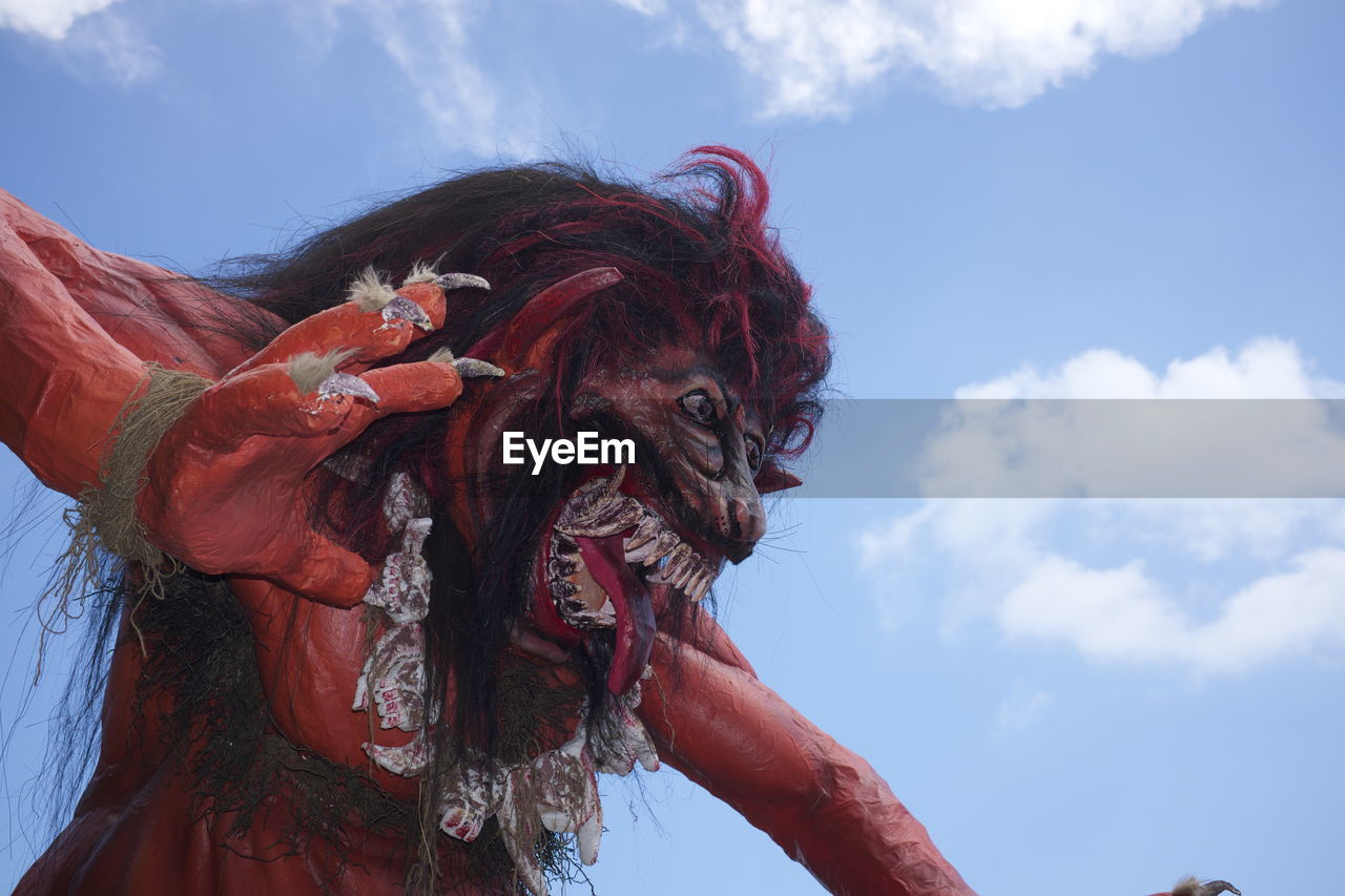 Low angle view of ogoh-ogoh demon statue against sky