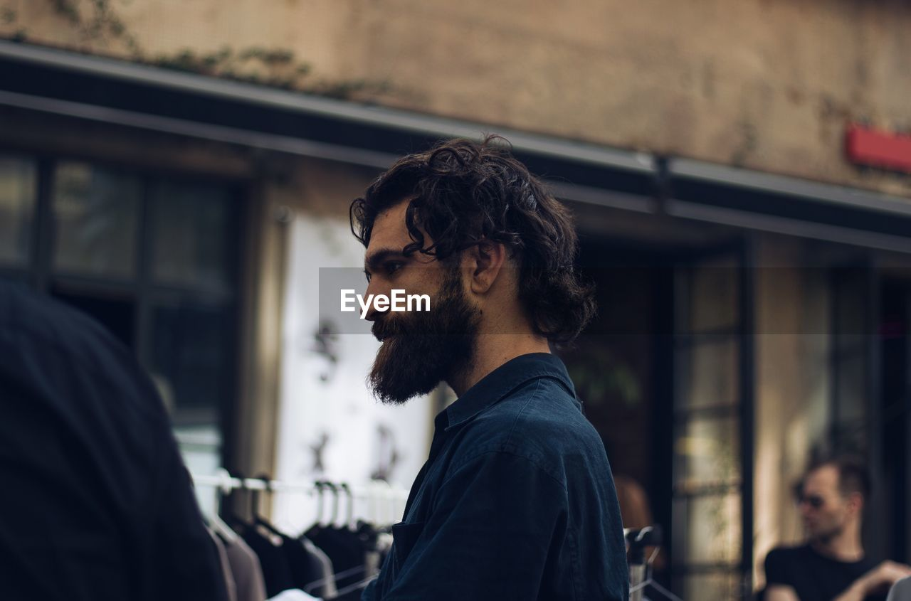 Side View Of Bearded Man Standing At Market