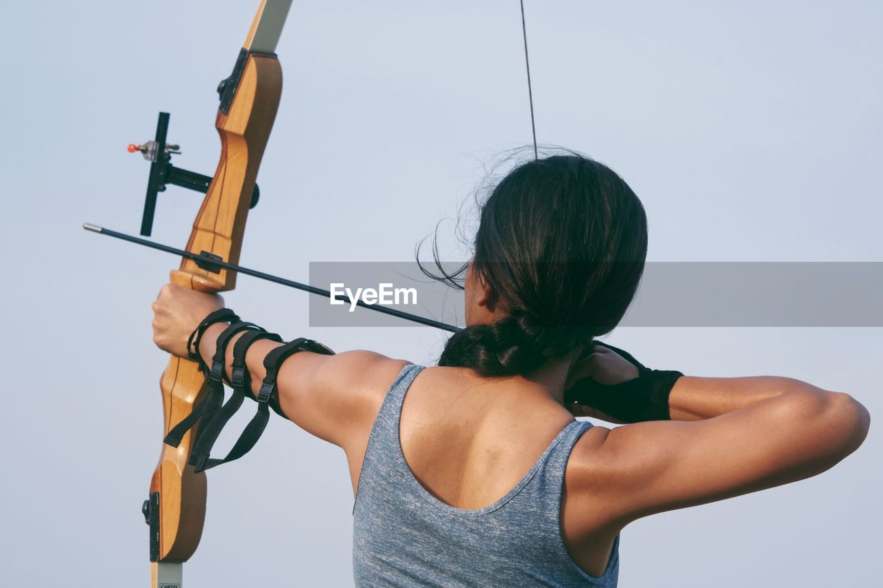 one person, lifestyles, sport, real people, leisure activity, sky, holding, young adult, nature, waist up, young women, aiming, women, adult, rear view, casual clothing, day, weapon, standing, arrow - bow and arrow, hairstyle
