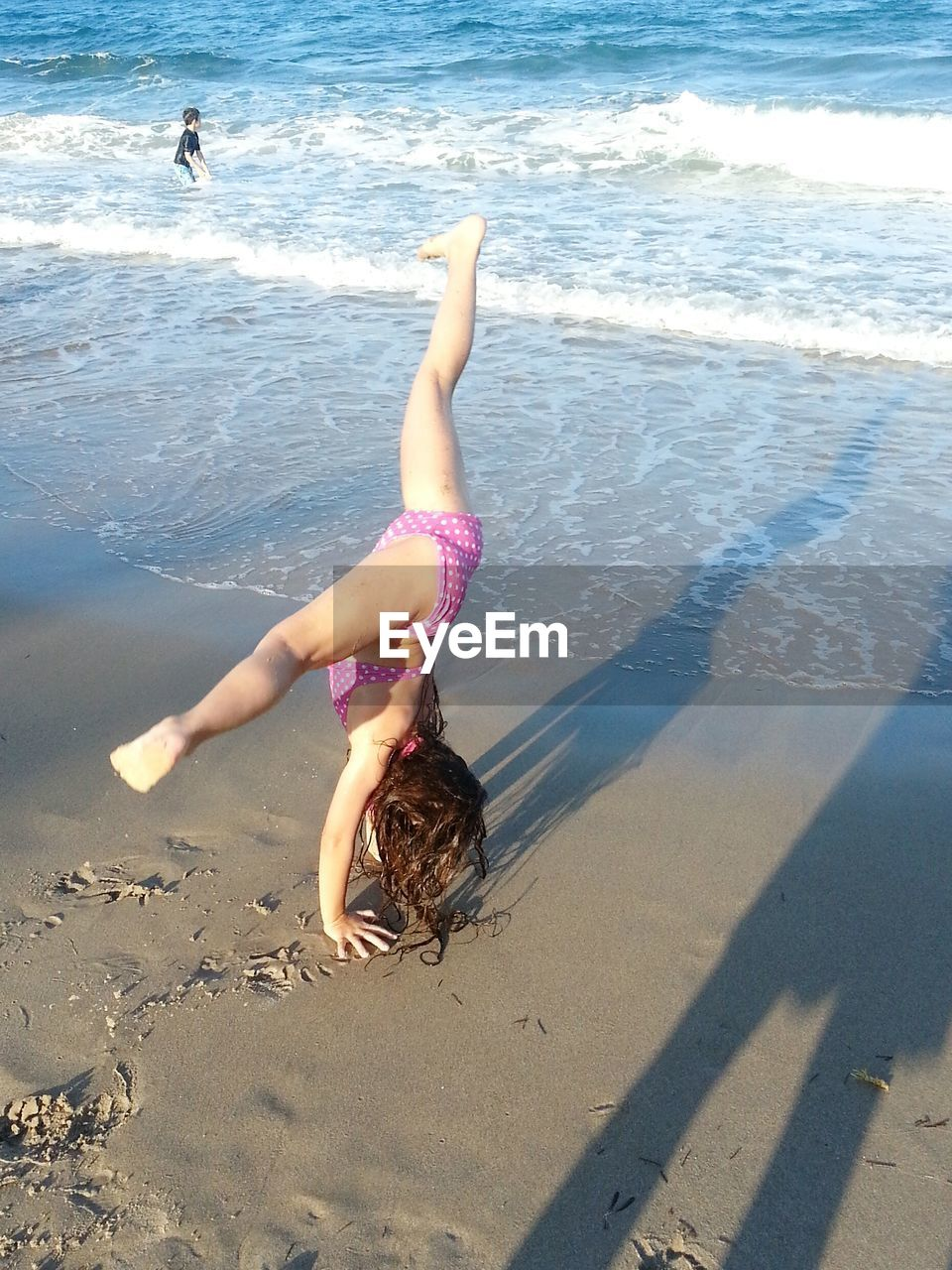 Girl In Bikini Doing Gymnastics At Beach