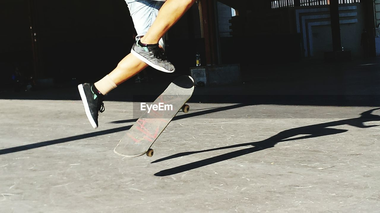 Low Section Of Man Jumping With Skate Board On Street