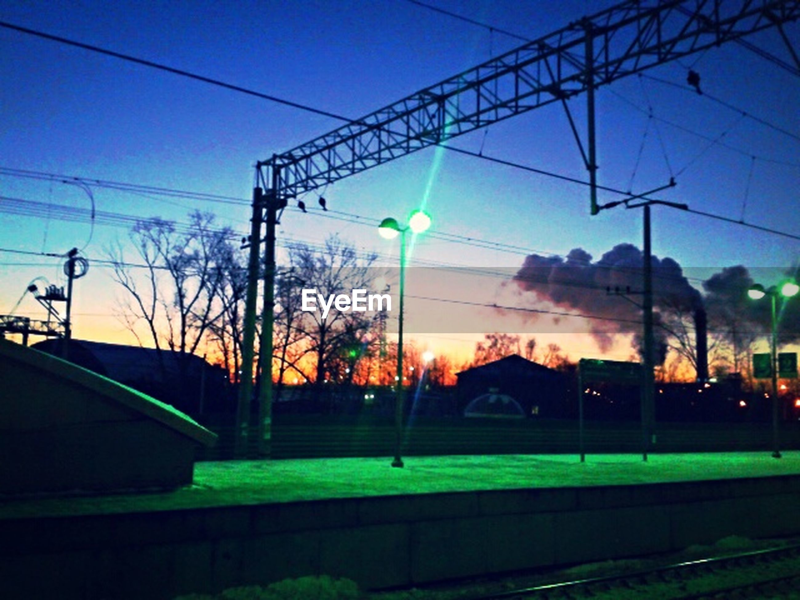power line, electricity pylon, transportation, electricity, railroad track, sunset, power supply, cable, sky, rail transportation, fuel and power generation, tree, street light, connection, clear sky, silhouette, power cable, public transportation, road, technology