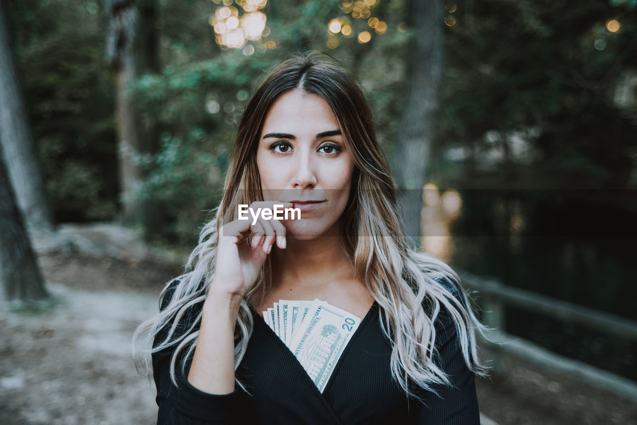 Portrait of beautiful young woman with paper currency standing in forest