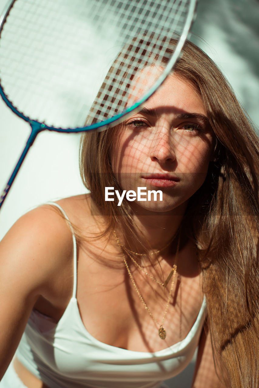 Close-up portrait of beautiful young woman holding racket