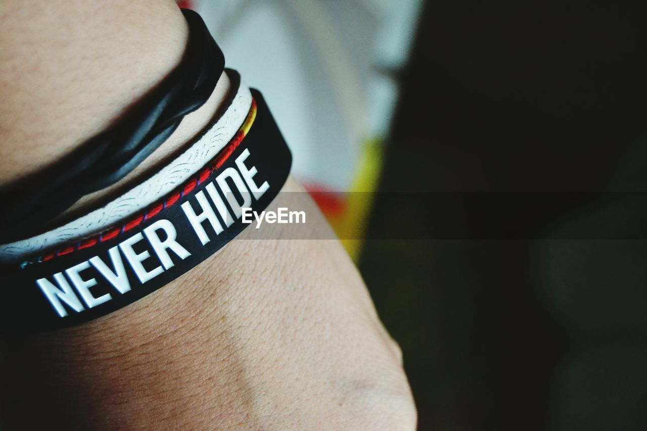 Cropped Image Of Hand Wearing Bracelet With Text