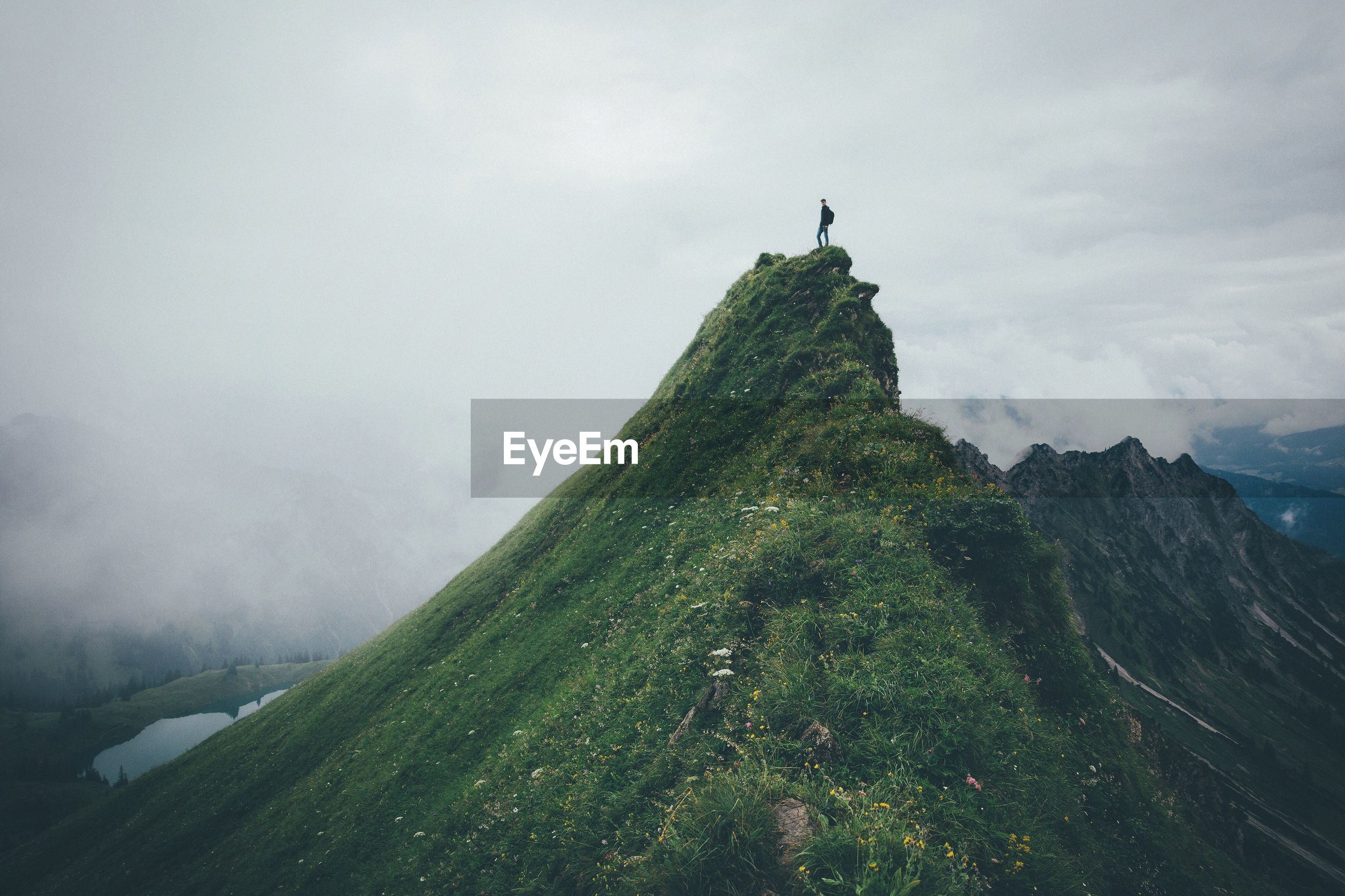 Man standing on mountain peak against cloudy sky
