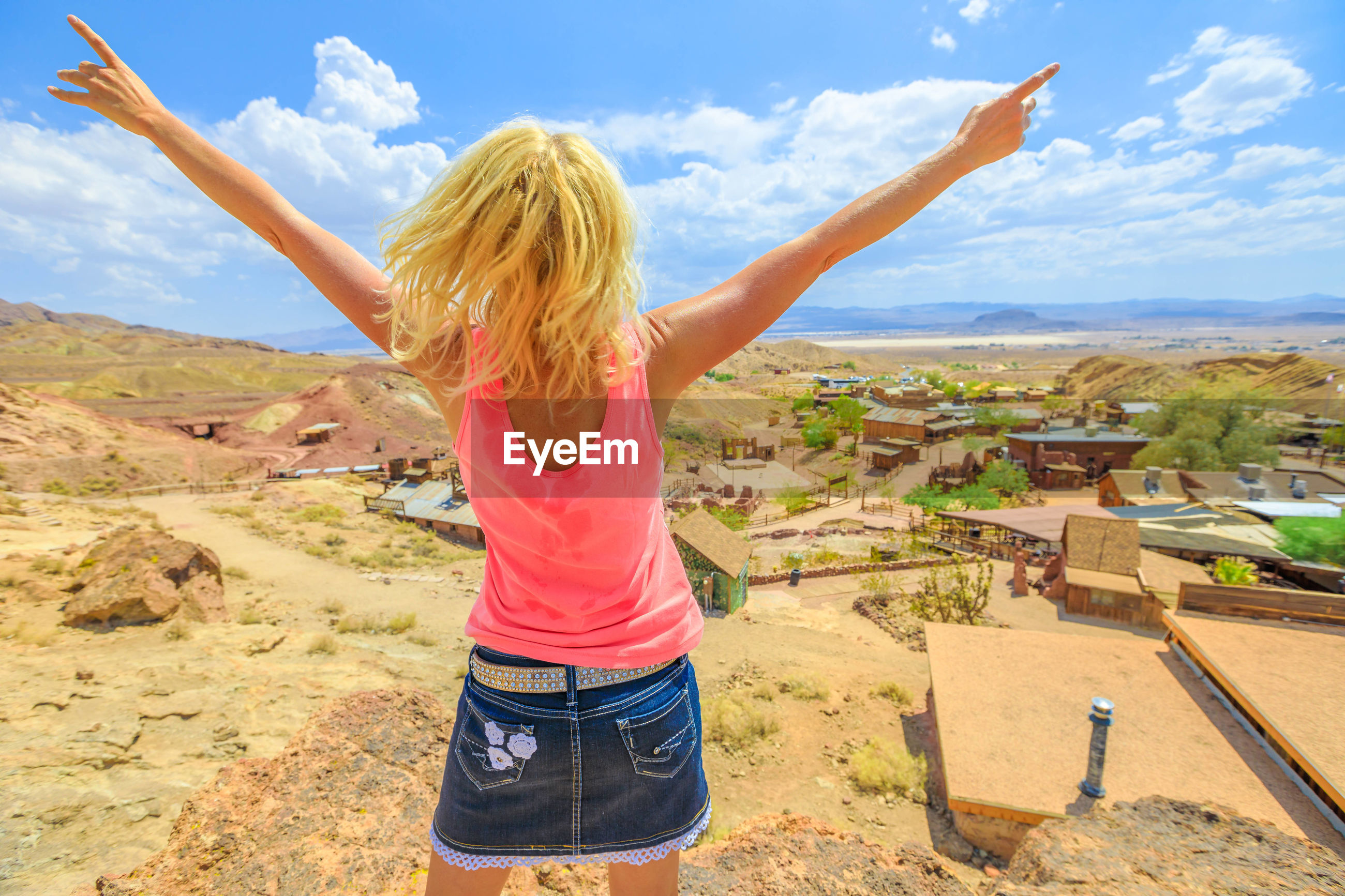 Rear view of mature woman with arms raised standing on mountain against blue sky during sunny day
