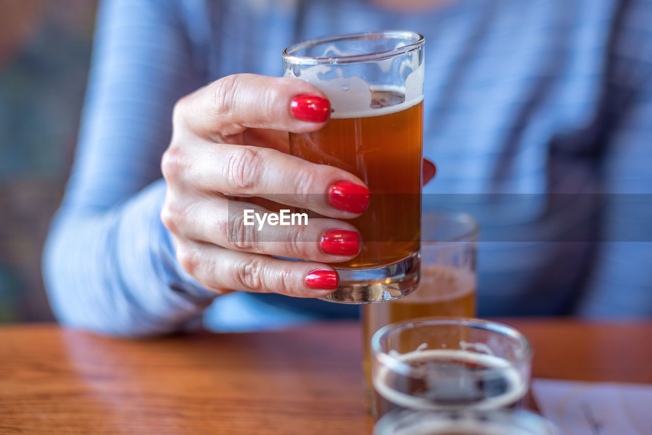 Close-up of woman holding glass of beer from flight at brewery