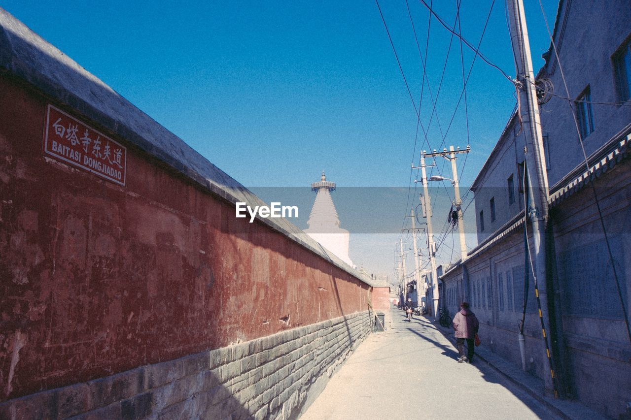 View Of Miaoying Temple Behind Wall Against Sky
