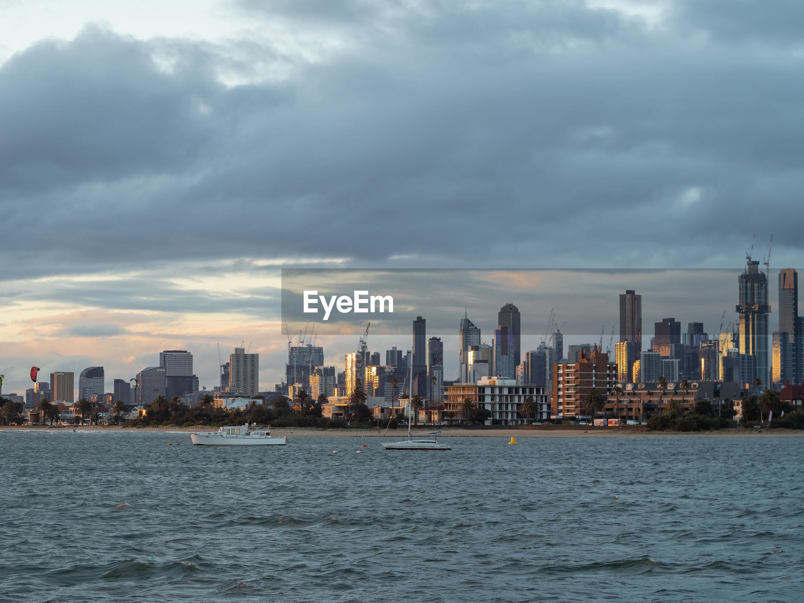 Sea by buildings against sky in city