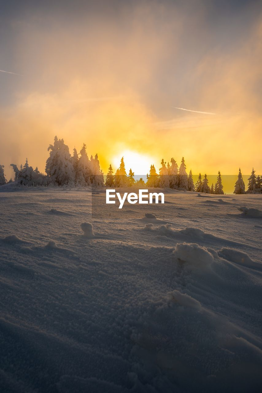 Idyllic shot of snow covered field against sky during sunset