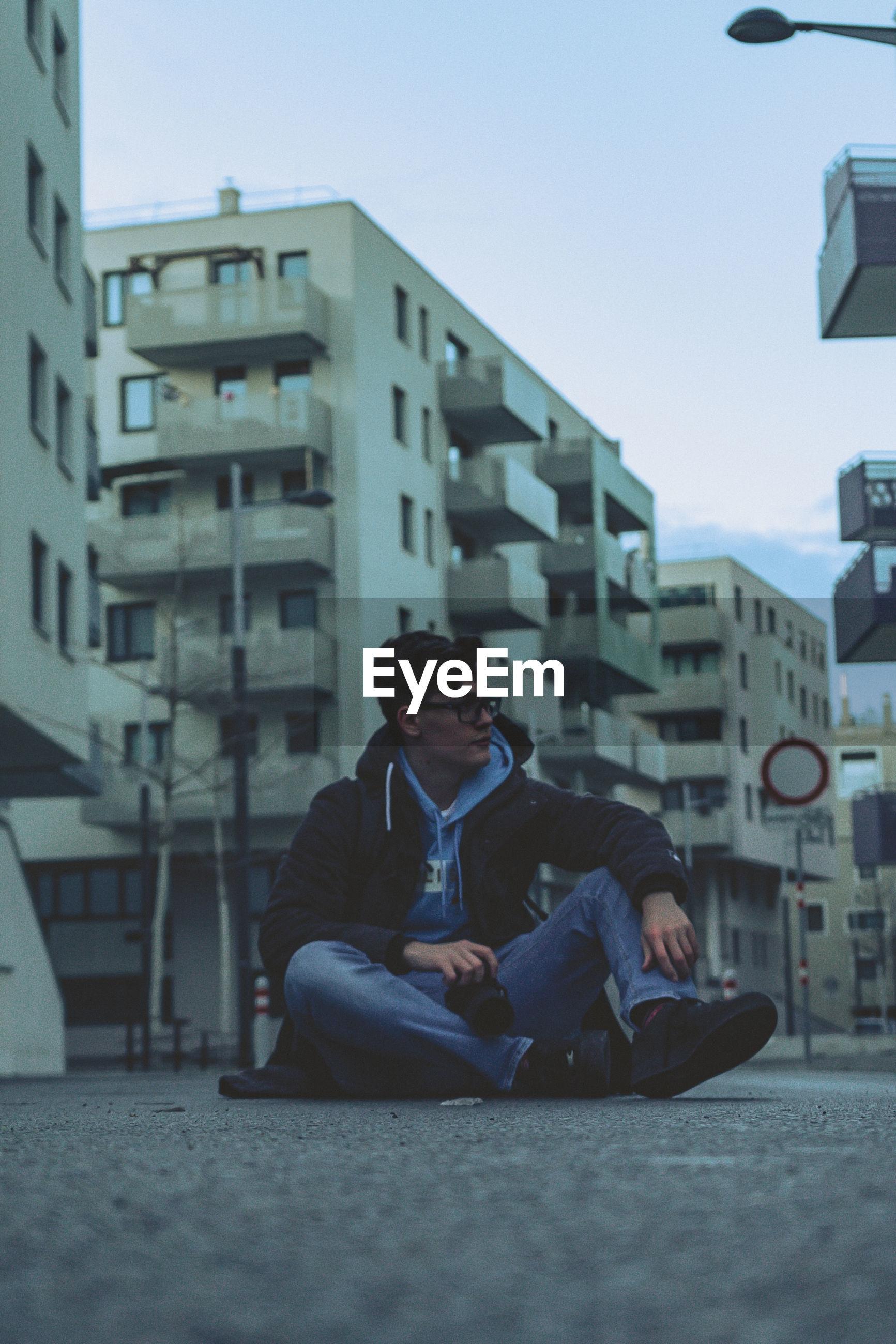 Man sitting against buildings in city