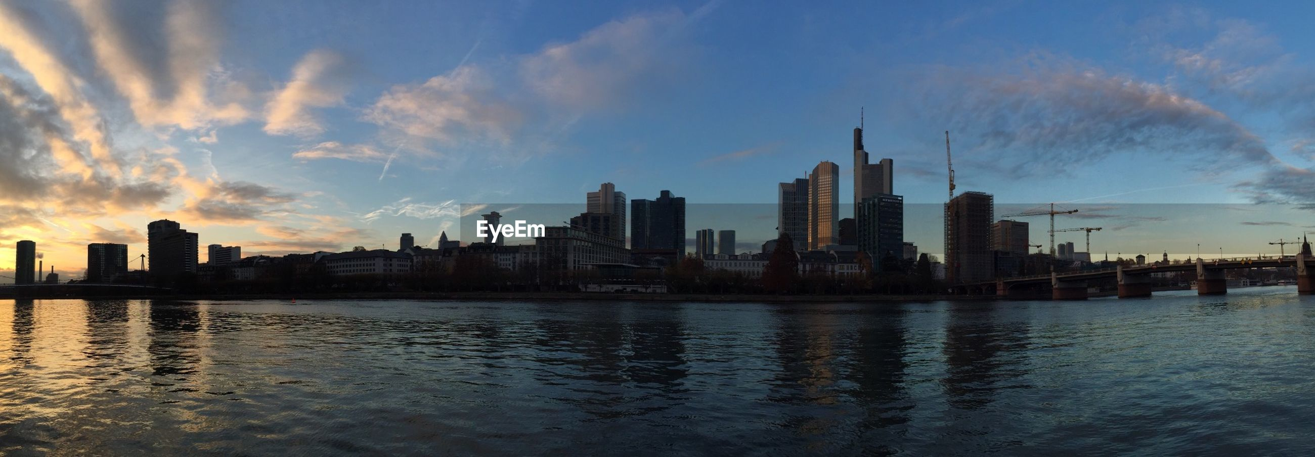 building exterior, architecture, city, built structure, water, skyscraper, sky, cityscape, waterfront, urban skyline, river, sunset, reflection, skyline, cloud - sky, modern, cloud, office building, tall - high, tower