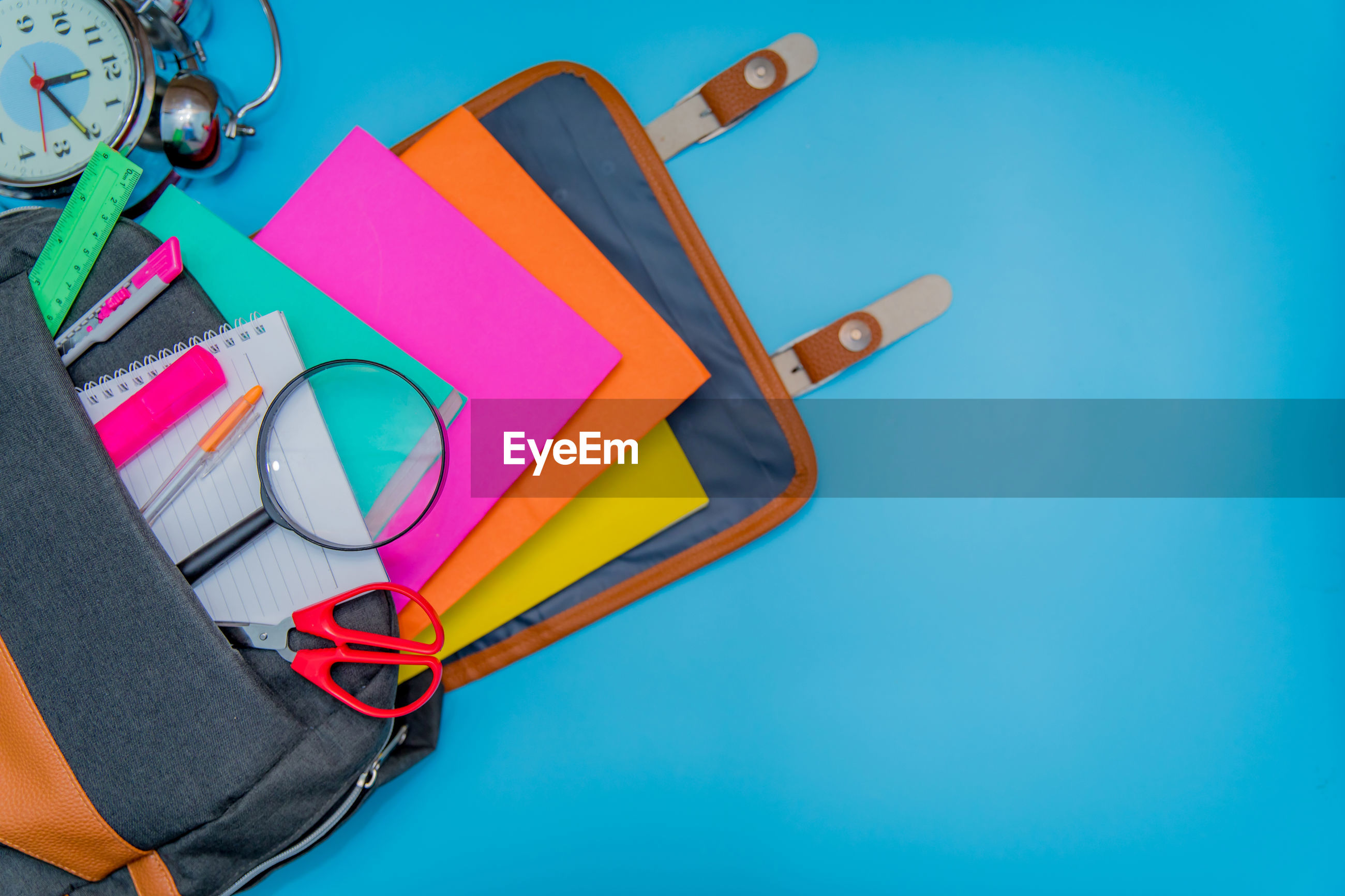 High angle view of multi colored school supplies over blue background