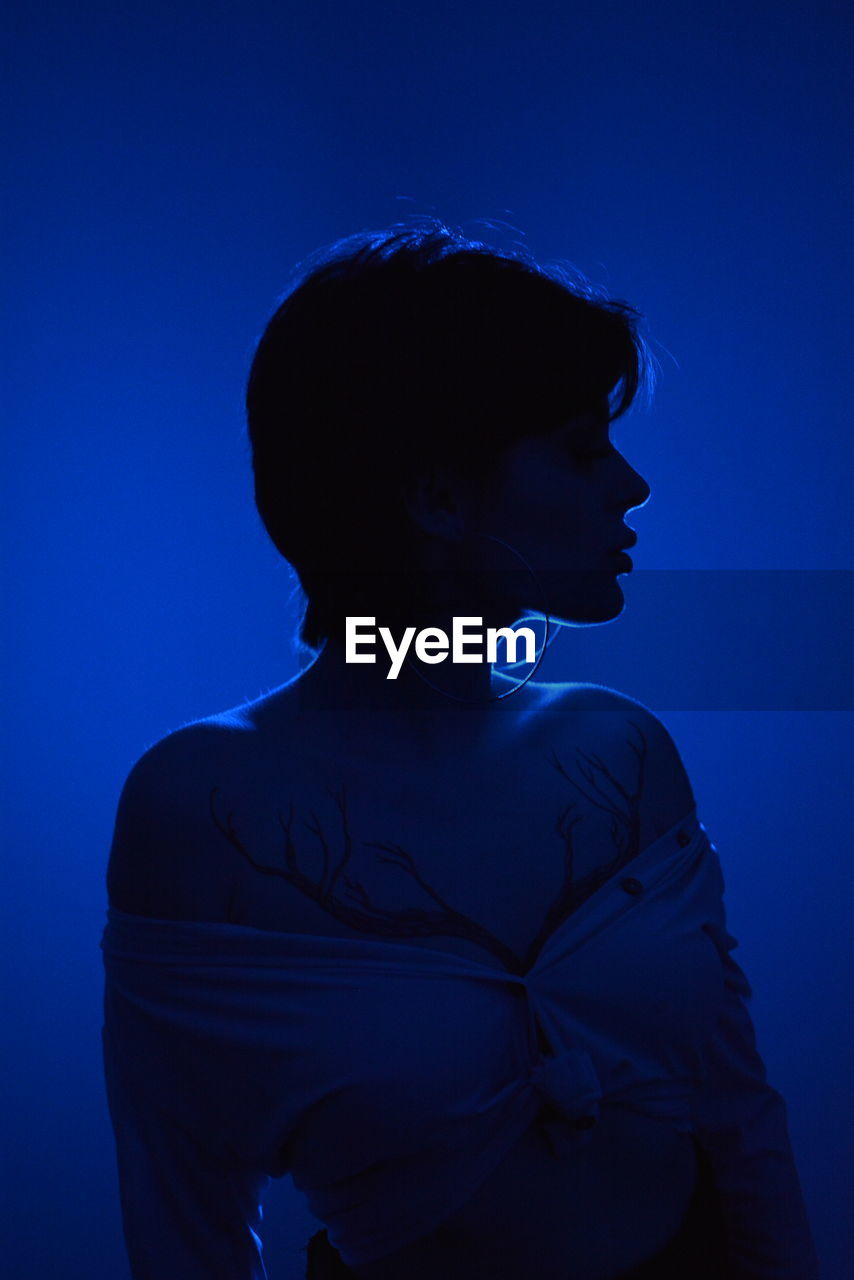 Woman looking away against blue background