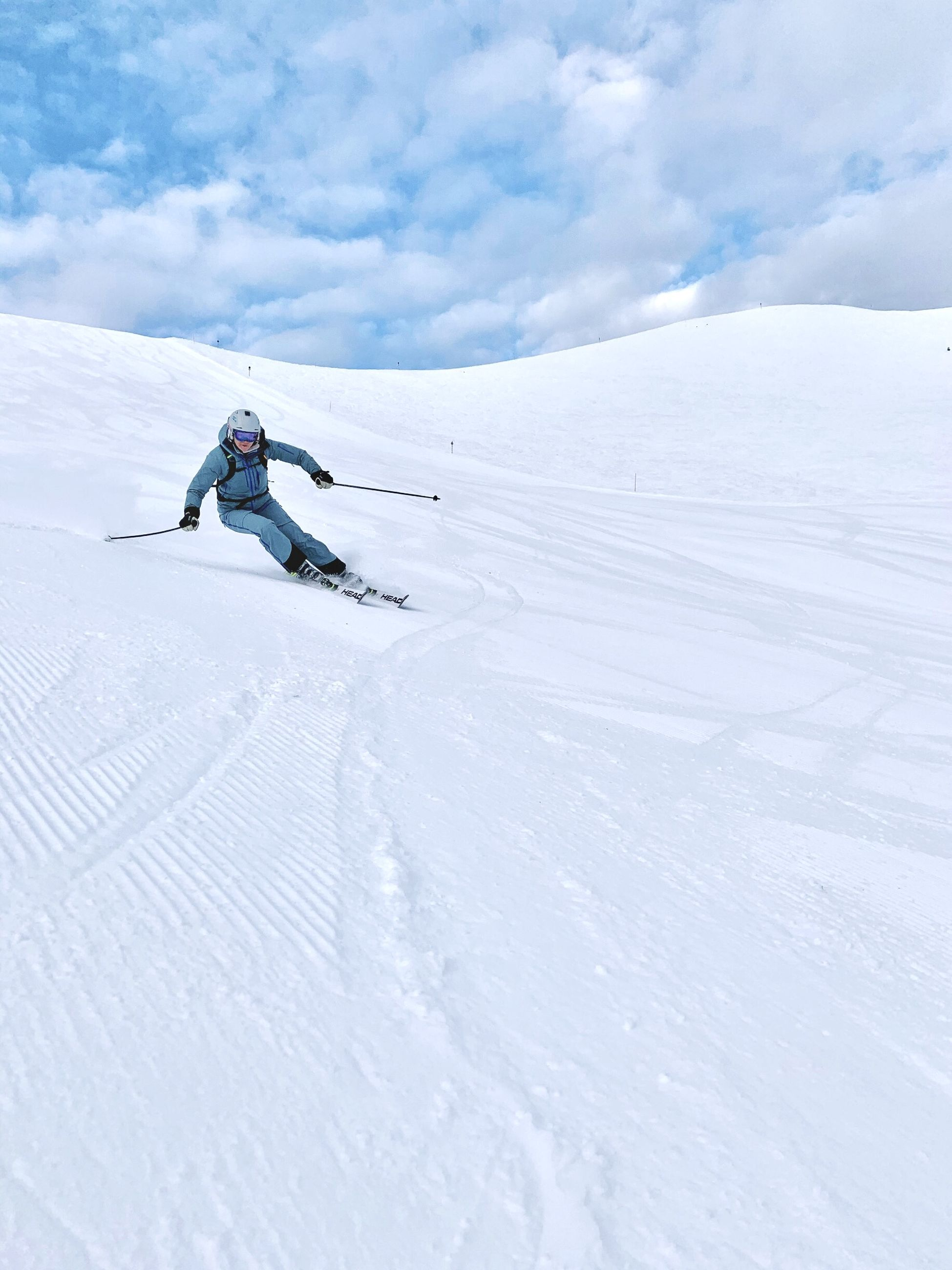 Woman skiing on snow covered mountain against sky