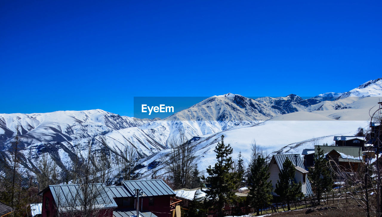winter, sky, cold temperature, mountain, snow, blue, scenics - nature, beauty in nature, clear sky, nature, mountain range, snowcapped mountain, architecture, built structure, tranquility, no people, day, building exterior, copy space, outdoors