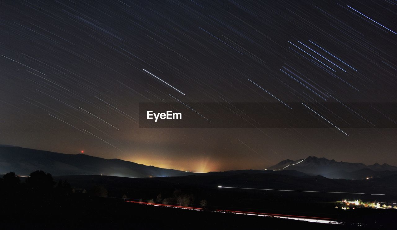 mountain, night, scenics, star - space, mountain range, beauty in nature, nature, illuminated, tranquil scene, motion, long exposure, sky, star trail, light trail, astronomy, outdoors, tranquility, no people, galaxy, star field, road, starry, constellation, space