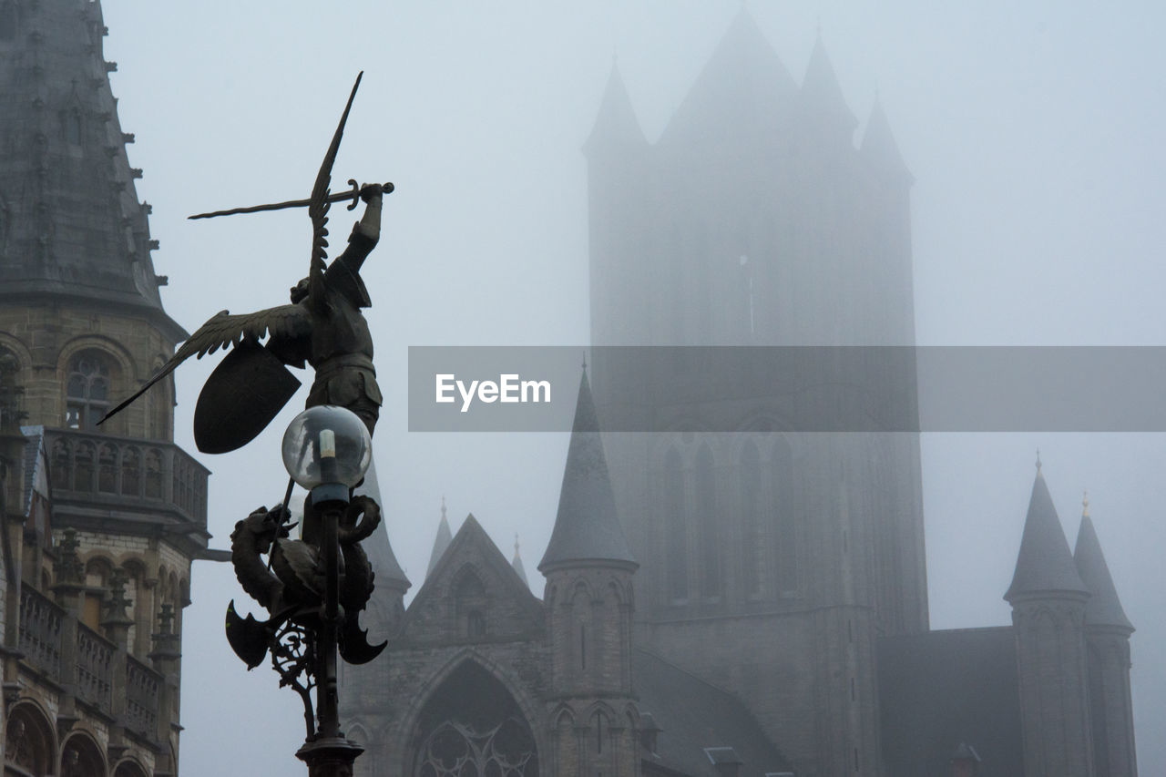 Low angle view of sculpture against buildings during foggy weather