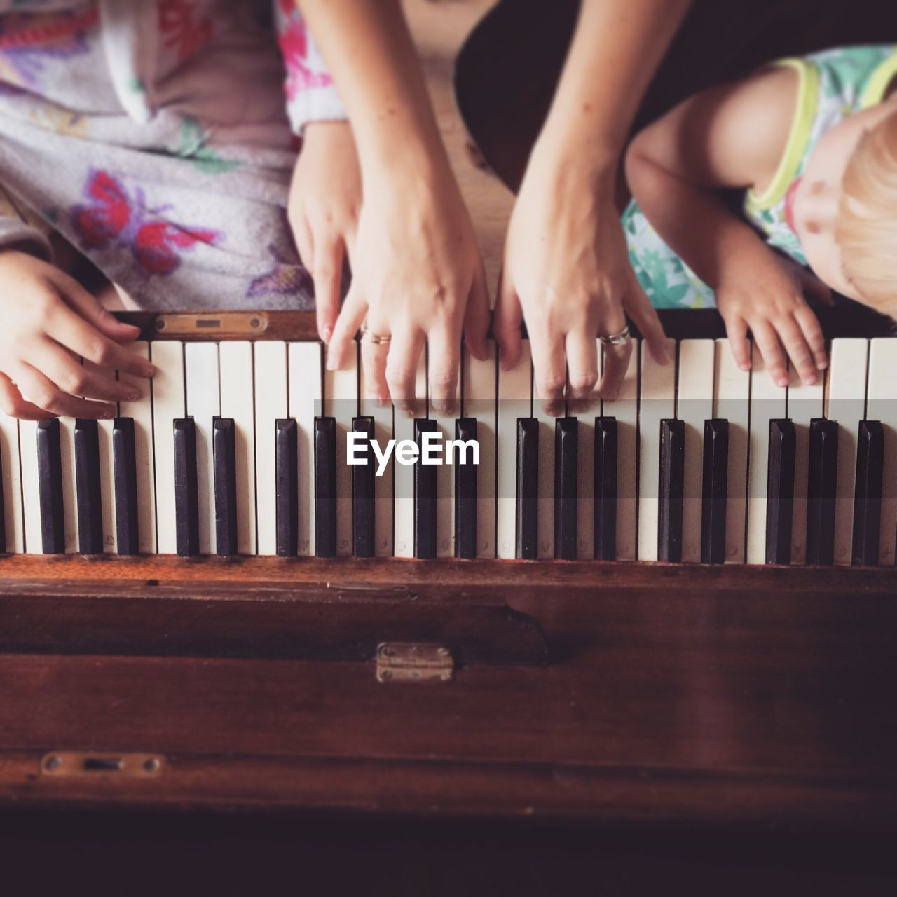 Cropped Image Of Mother Teaching Daughters To Play Piano